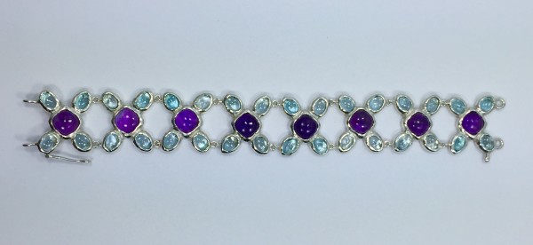 "VD - Bracelet. Sterling silver link bracelet with 32 light blue topaz cabochons and 8 amethyst cabochons. 7.5"" in length"